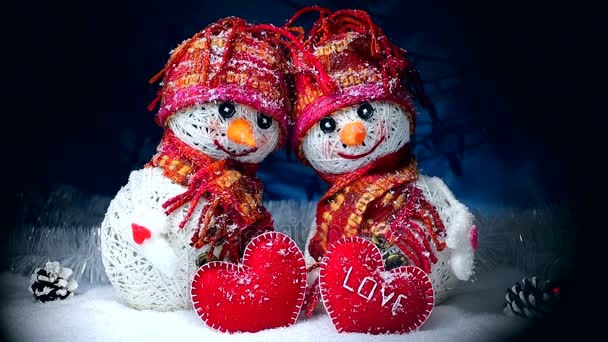 Valentines Day. Snowmen in love stand on the snow and keep their hearts out of felt on a dark background