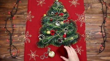 a small christmas tree of tinsel nuts ribbons and ornaments gift for a
