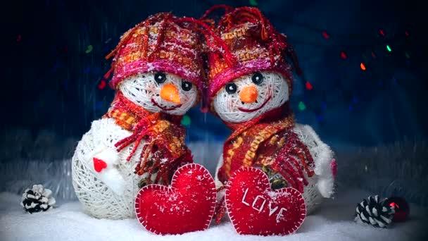 Valentin-nap. Hóembert, a szerelem állni a hóban, és tartsa a szívüket, szövött, sötét háttér előtt