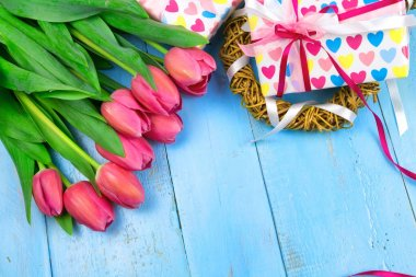 Bouquet of tulips on blue wooden table with gift box. Happy womens day. 8 March., Mothers Day. Flat lay and copy space