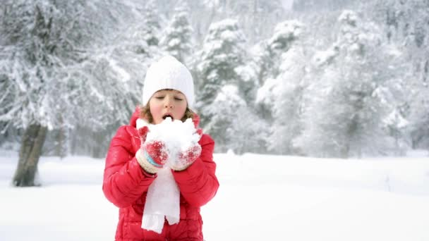 little girl blowing snow