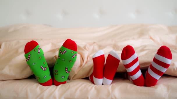 family in christmas socks in bed
