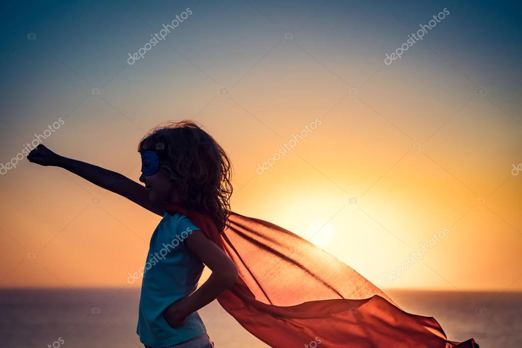 Superhero child on beach