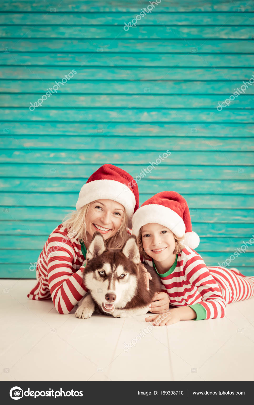 b41fdca05ea3 Ευτυχισμένη μητέρα με παιδί ντυμένος με Αϊ Βασίλη καπέλο και σκυλί που  ξαπλώνει στο πάτωμα την παραμονή των Χριστουγέννων