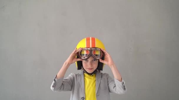 Boldog gyerek versenysisakban és szemüvegben. A kölyök ünnepli a győzelmet. Győztes és sikeres koncepció. Lassú mozgás.