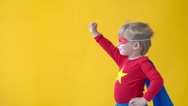 Szuperhős gyerek sárga háttérrel. Egy szuperhős kölyök lassú mozgású fotózása. Képzelet és szabadság fogalma