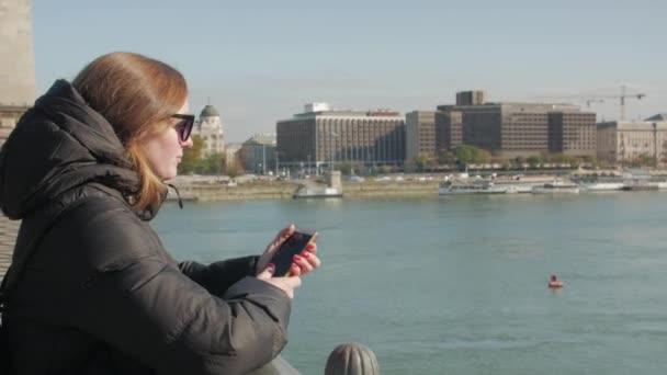 Lány telefonnal a hídon
