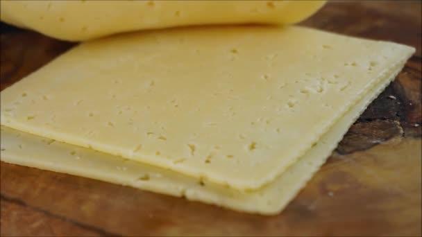 čerstvý sýr krájený na dřevěné desce. vrstvy na sobě na tmavém pozadí
