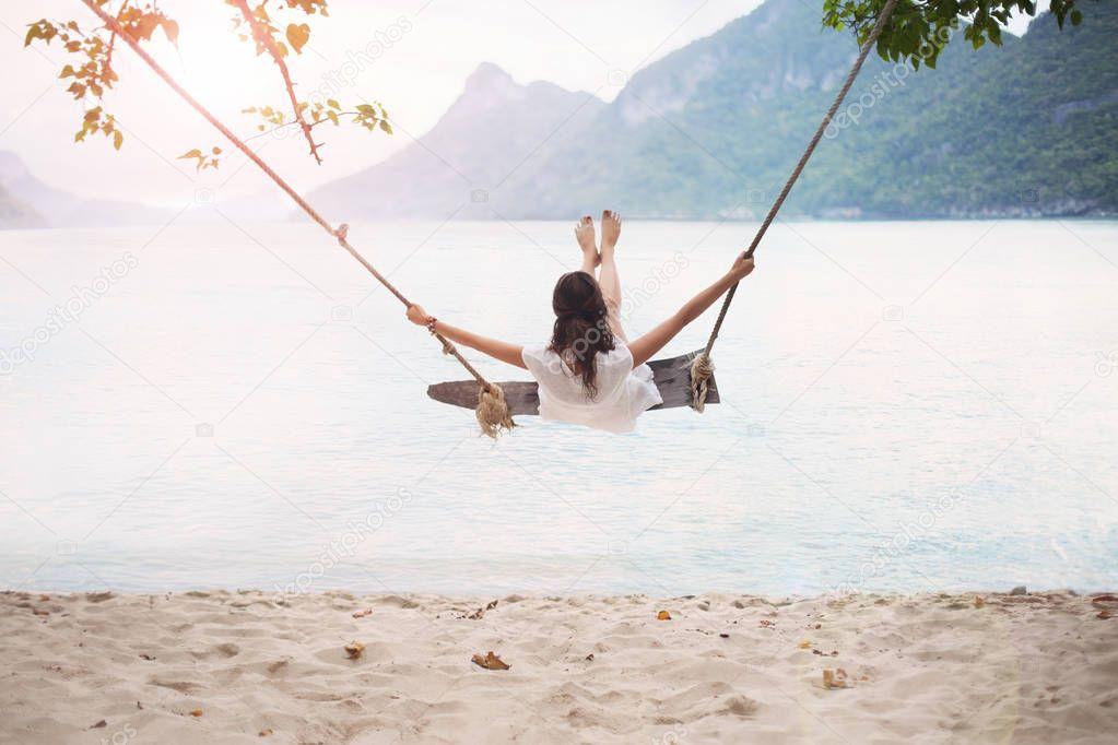 Carefree happy woman swinging
