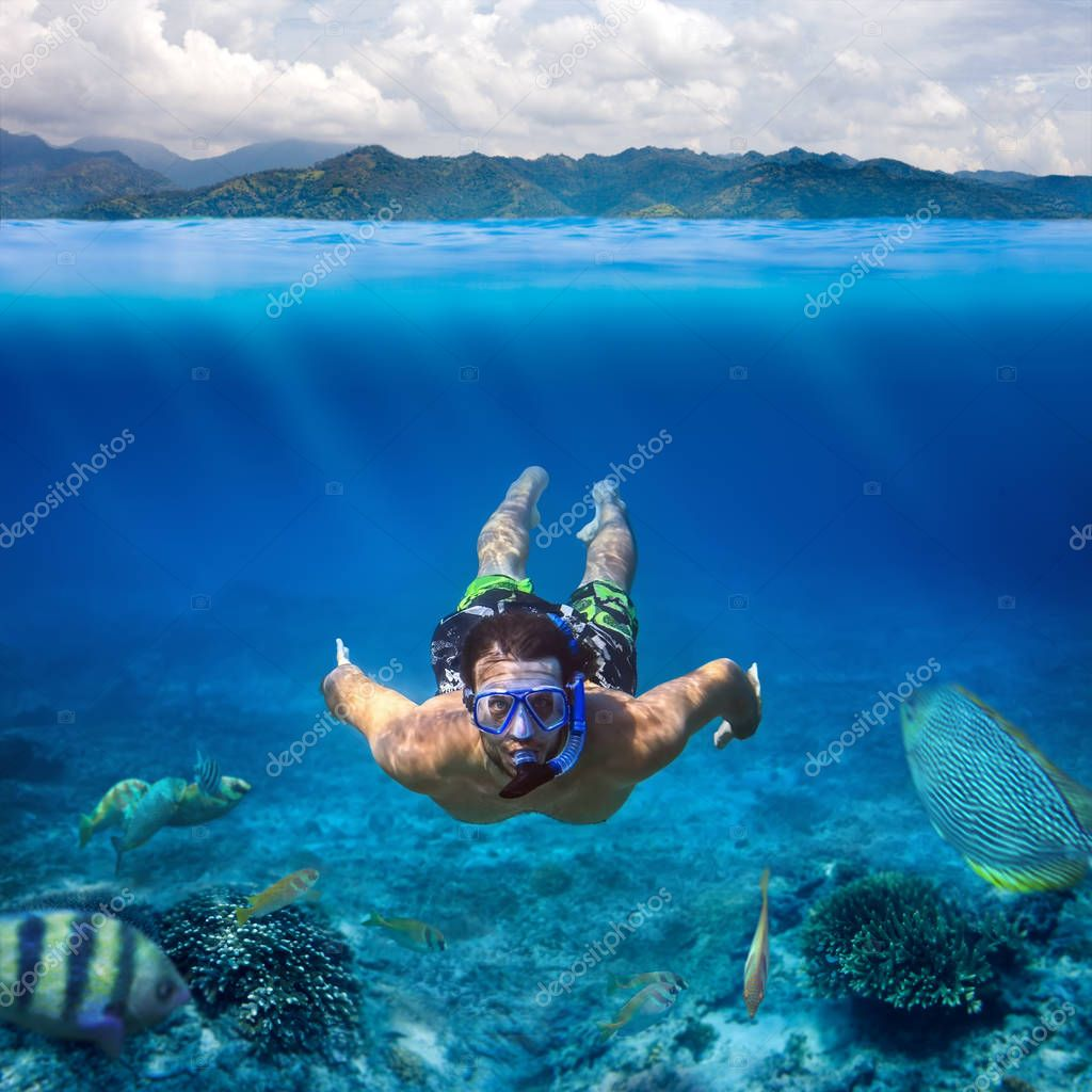 young man snorkeling in sea