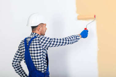 painter man painting wall in beige