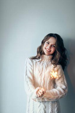 woman holding festive sparkler
