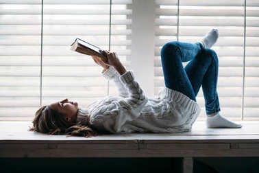 woman reading book lying on window sill at home