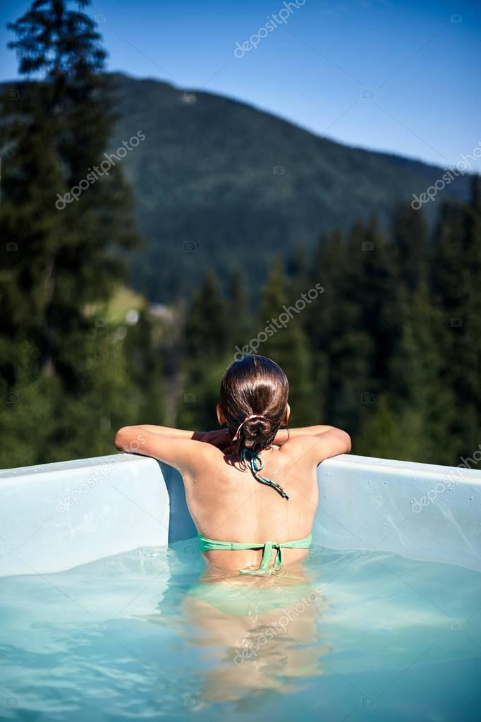 Young girl in pool looking at forest, back view. Young lady swimming, enjoying water spa treatments and resting in open air. Weekend, vacations outdoors concept.