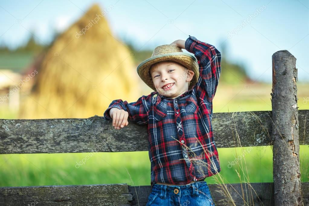 Close up portrait of little boy in hat with straw in mouth leaned on wooden fence. Happy chilhood concept. Vacatio