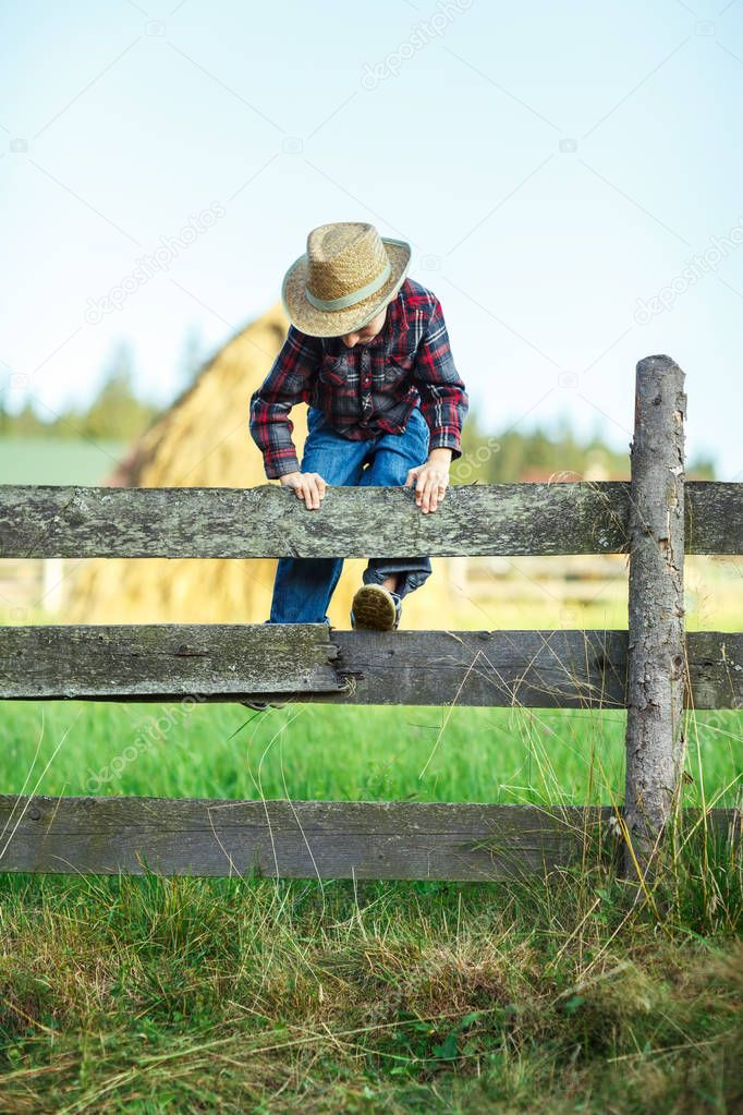 Small cowboy climbs over wooden fence, outdoor. Boy plays outdoors on wooden hedge with haystacks backdrop. Little traveler explores new opportunities