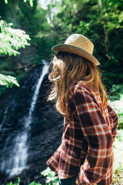 Back view of young girl in shirt and straw hat from afar admires waterfall. Caucasian young lady looks at falling water, photo on fresh air. Portrait of youth adolescent in wild nature
