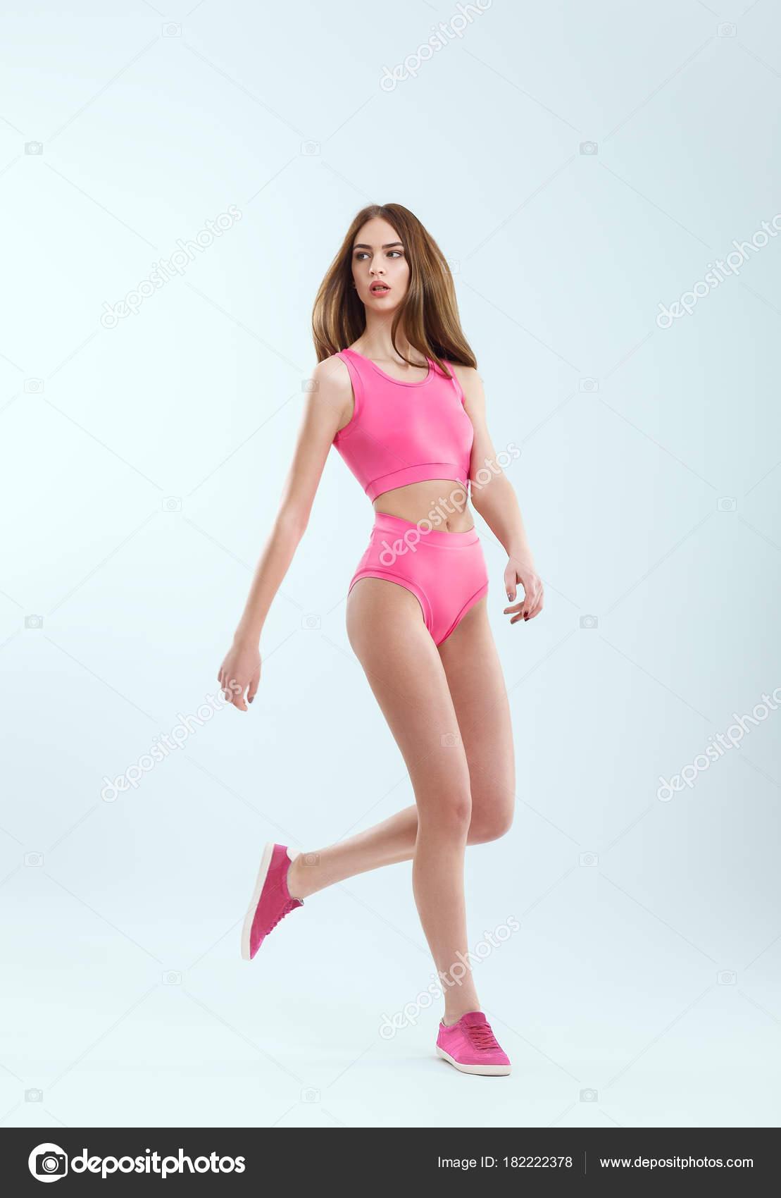 fc8f8dc0daa Полная длина Портрет молодой красивой девушки в розовый купальник в движении.  Стройная девушка Кавказа в спортивной одежде для фитнес