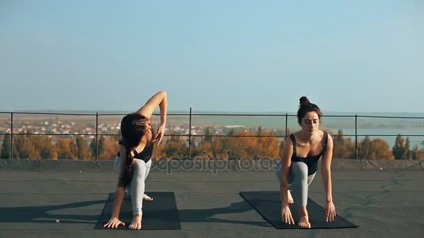 Dvě krásné ženy cvičí jógu asana na střeše, venku ráno. Úhlové pozice hatha jógy. Prospěch, zdraví, cvičení koncept. Partner jóga