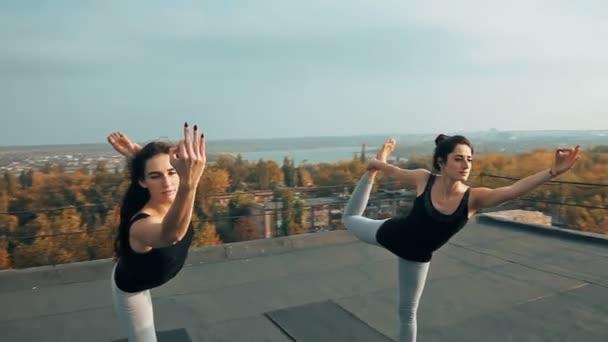 Dvě krásné ženy cvičí jógu asana natarajasana na střeše, venku ráno. Hatha jóga provádí dvě štíhlé dívky. Harmonii se světem, soul, energetické koncepce