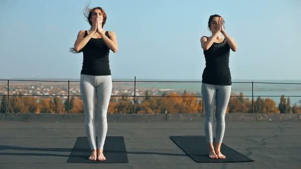 Dvě mladé ženy cvičí jógu asana hasta uttanasana (zvednuté ruce představují) na střeše, venku. Stylový symetrických cvičení pro tělo i ducha po ránu
