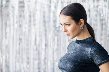 Side view of confident young woman on blurred background