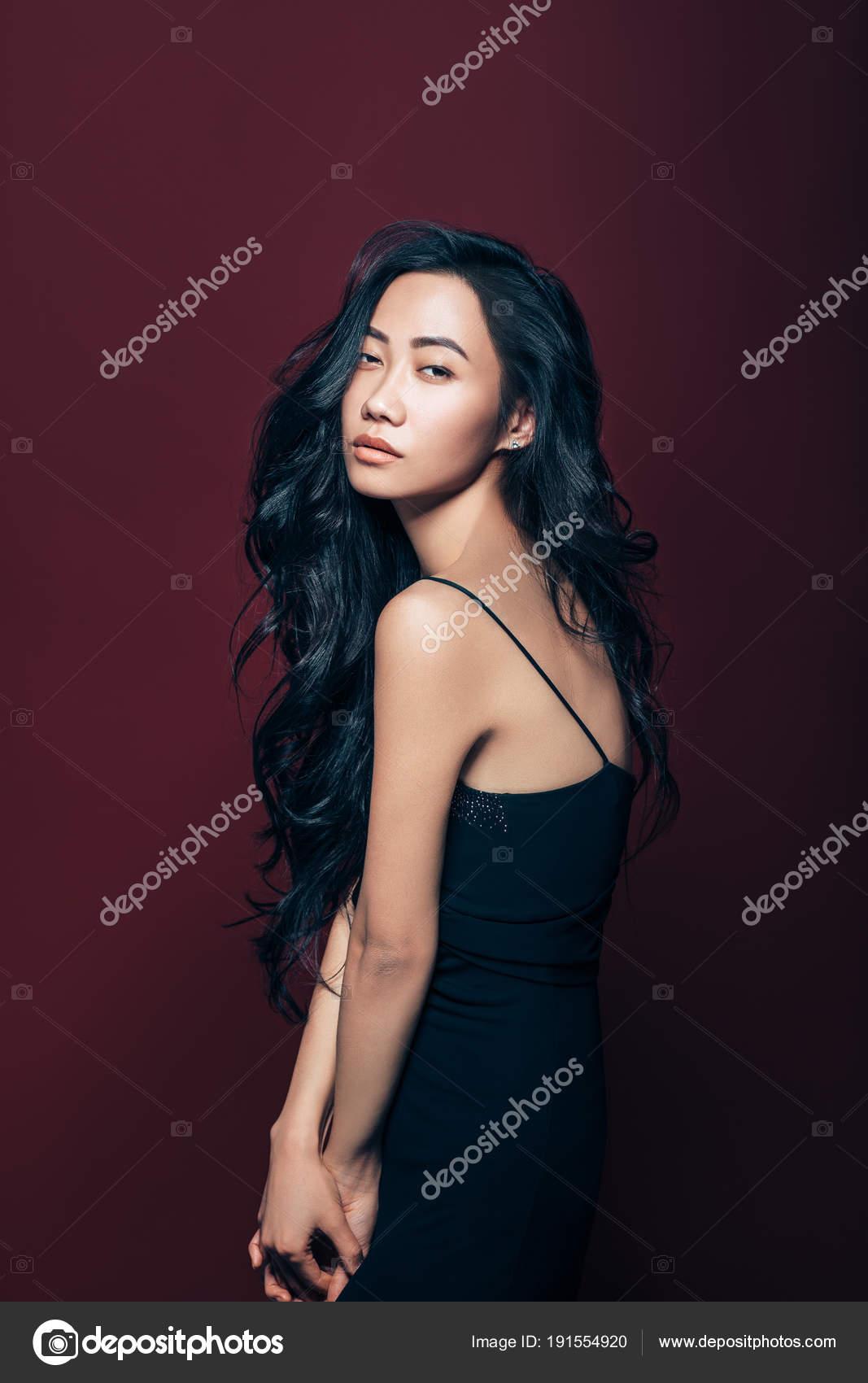 f5da179ccb58c6 Красиві азіатські жінки в чорне плаття в студії на фоні коричневий себе.  Дуже модні моделі портрет — Фото від ...