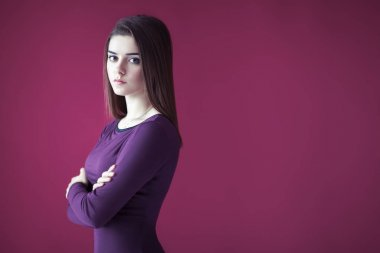Portrait of beautiful serious woman with crossed arms on pink background. Copy space