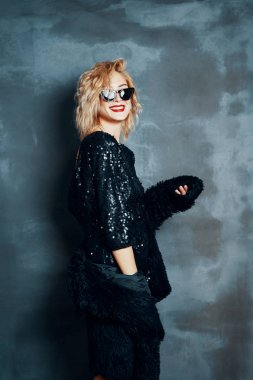 Pretty blonde woman in little black dress posing on grey background