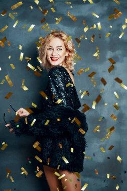 Pretty blonde woman in little black dress dancing on confetti, party, fun, celebration concept