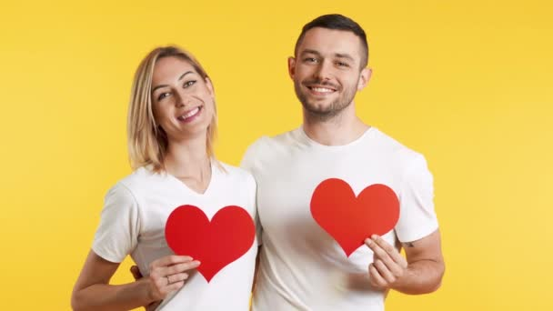 Young couple in love holding big paper hearts in hands over studio background. relationship concept