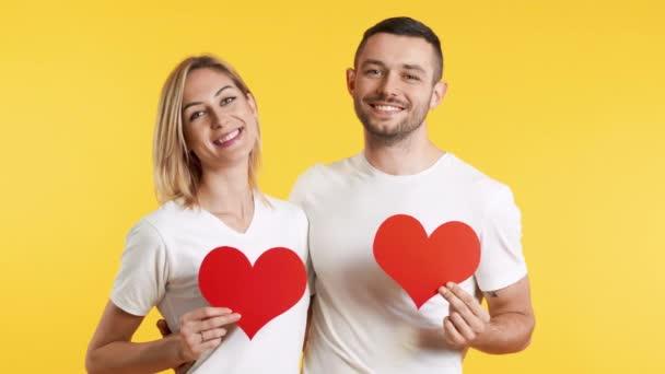 Mladý pár v lásce drží velké papírové srdce v rukou nad studiem pozadí. koncept vztahu