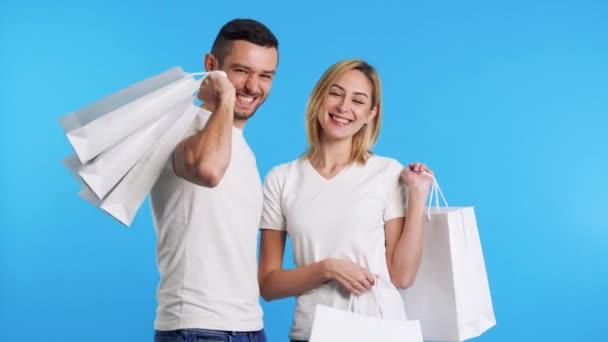 Mladý šťastný pár držící nákupní tašky vychutnat své nákupy izolované přes modré pozadí. prodej, nakupování, nákupní koncept