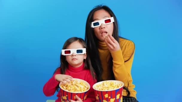 Glücklich lächelnde Mutter und ihre kleine Tochter in 3D-Brille mit Popcorn vor dem Fernseher
