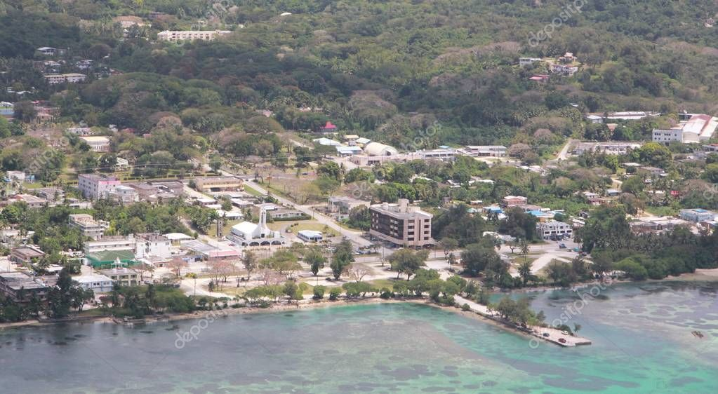 The Fishing Base dock juts out of the clear green and blue waters of Saipan lagoon, with a background of the buildings