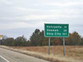 Roadside sign with distances to Henryetta, Okema and Oklahoma City.