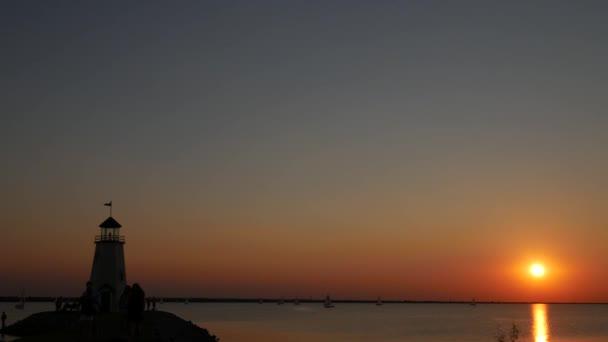Stetige Aufnahme, Silhouette eines Leuchtturms und ein schöner Sonnenuntergang über dem See