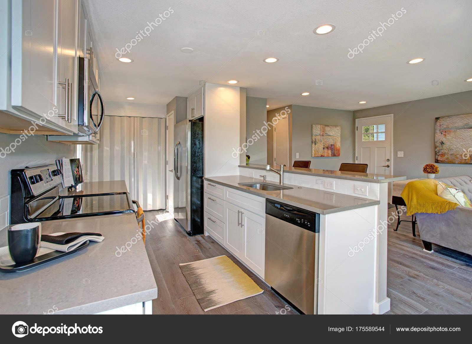 Leicht Gefüllte Küche Mit Edelstahl Geräte, Weiße Schränke, Garniert Mit  Quarz Zähler Und Hartholz Fußboden U2014 Foto Von Alabn