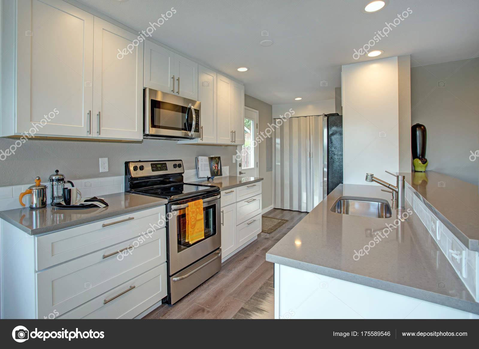 Piena luce cucina con elettrodomestici in acciaio inossidabile ...