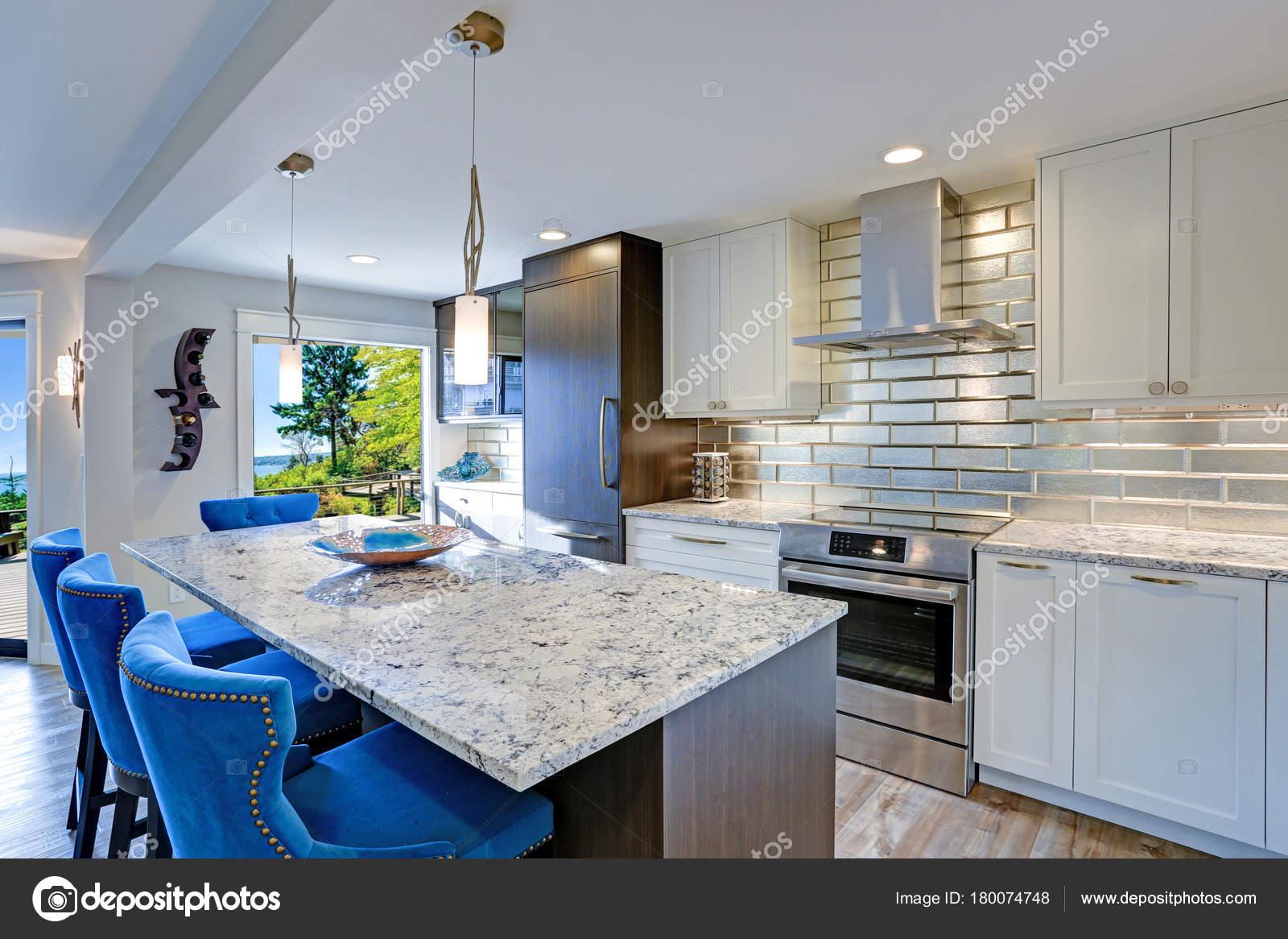 Gut Ausgestattete Küche Verfügt über Eine Große Kücheinsel Gekrönt Mit  Einer Grauen Quarzit Arbeitsplatte Und Flankiert Von Blau Getuftet  Esszimmerstühle ...