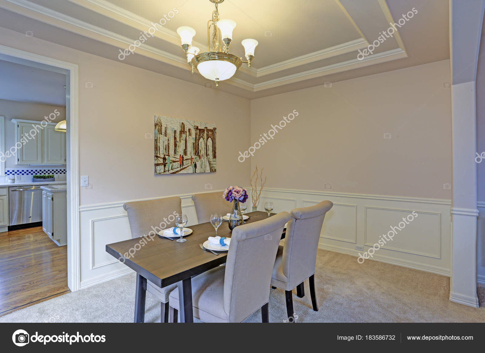 Chic Dining Room Accented With Wall Panel Mouldings And Tray Ceiling.