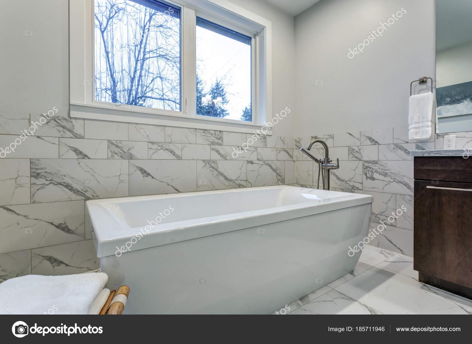 Ongelooflijke master badkamer met carrara marmeren tegel surround