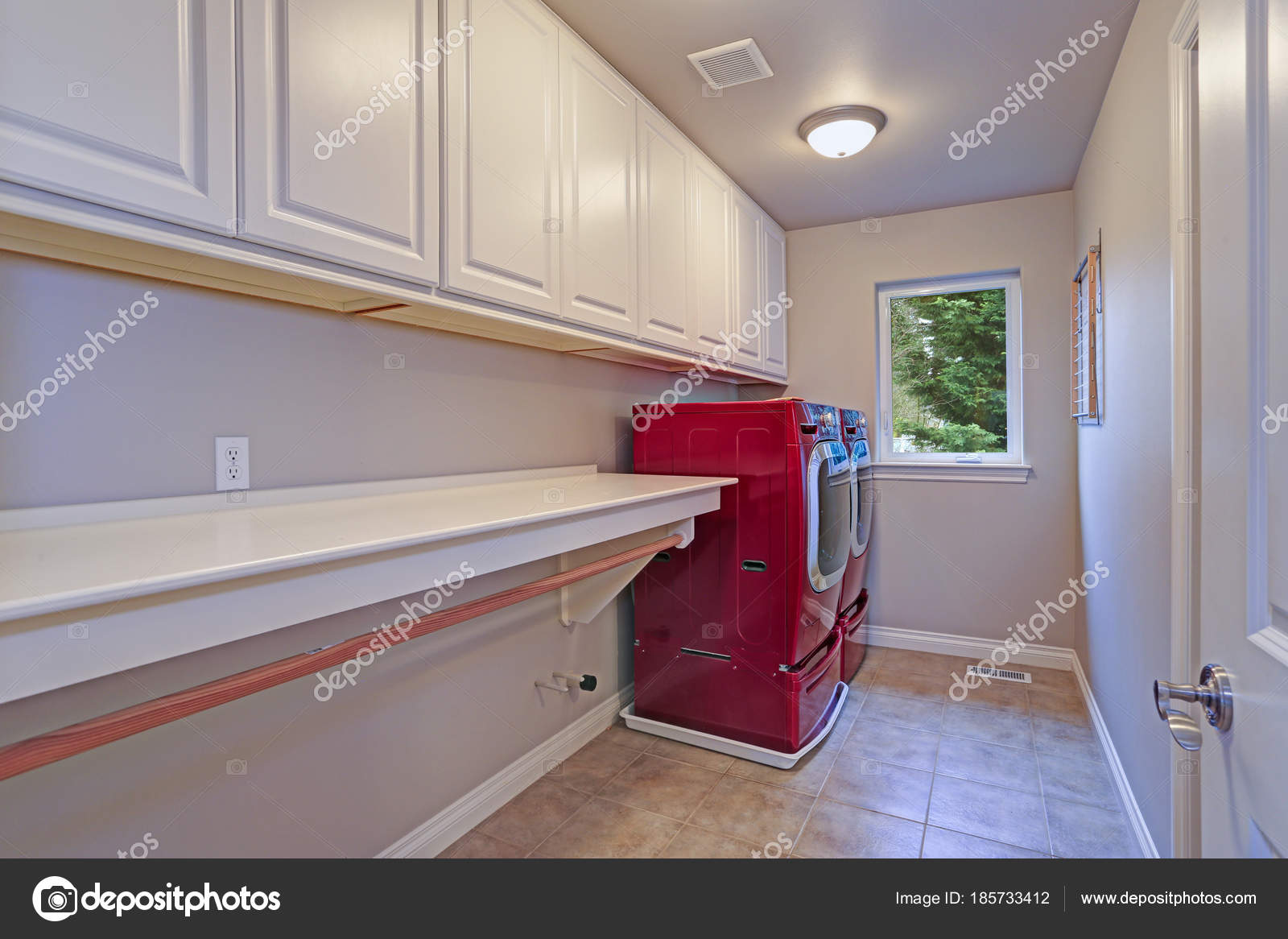 narrow home laundry with white cabinets and red accent laundry rh depositphotos com White Laundry Room Cabinets White Laundry Room