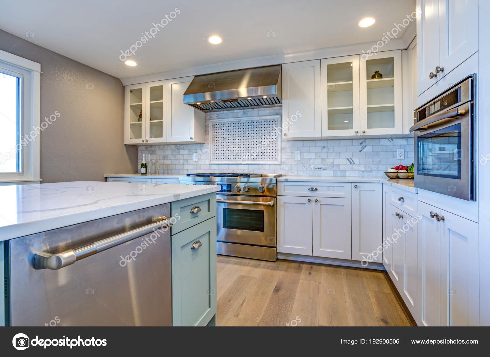 Cucina bianca con cappa in acciaio inox sopra piano cottura a gas ...