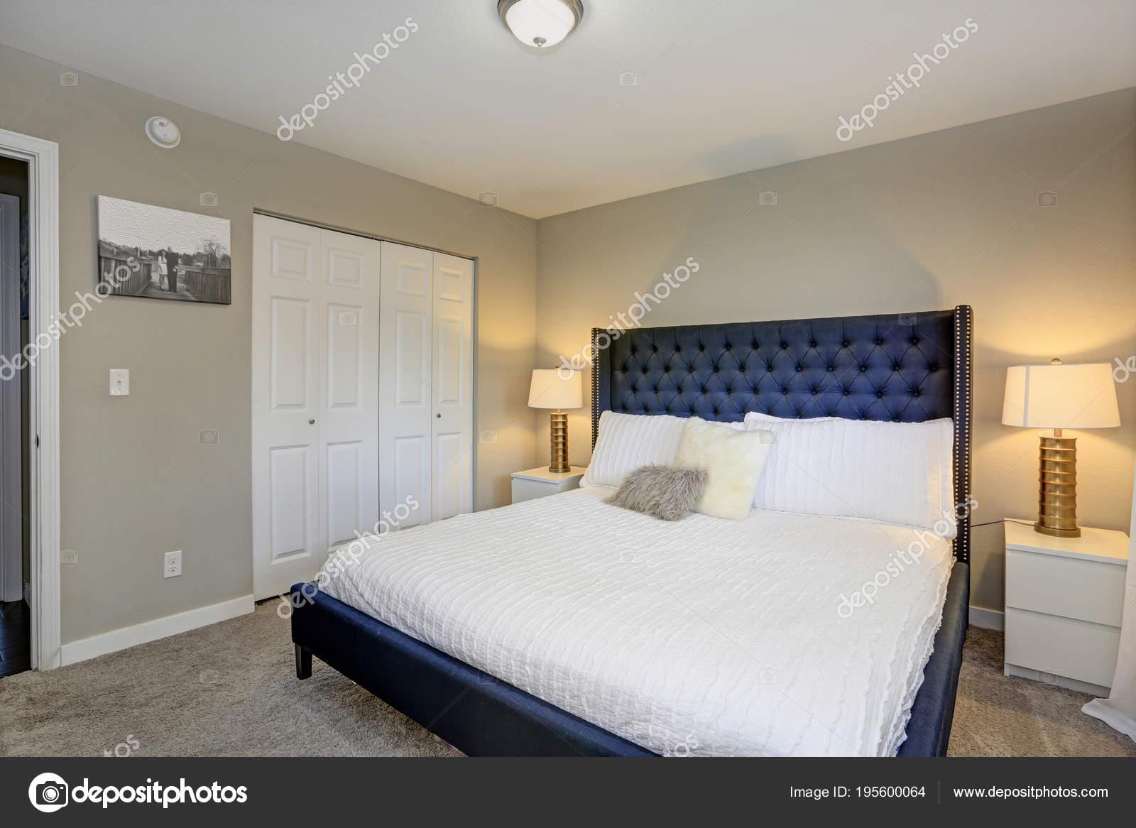 gezellige slaapkamer beschikt over een zwarte bed en beige muren stockfoto
