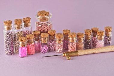 Beige, pink and yellow beads in glass jars on a bright purple background. Beads in a transparent container with a wooden cork. The concept of orderliness, balance and chaos.