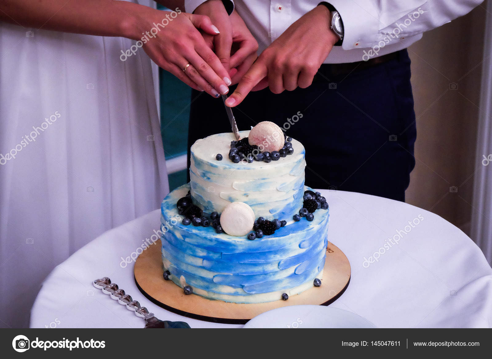 Two- tier blue cream wedding cake decorated with blueberries and ...