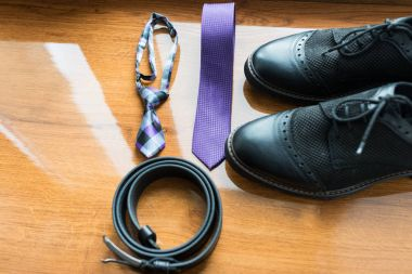 The groom's and a dogs wedding accessories. Lilac neck tie and a black leather belt and black shoes on a wooden background.