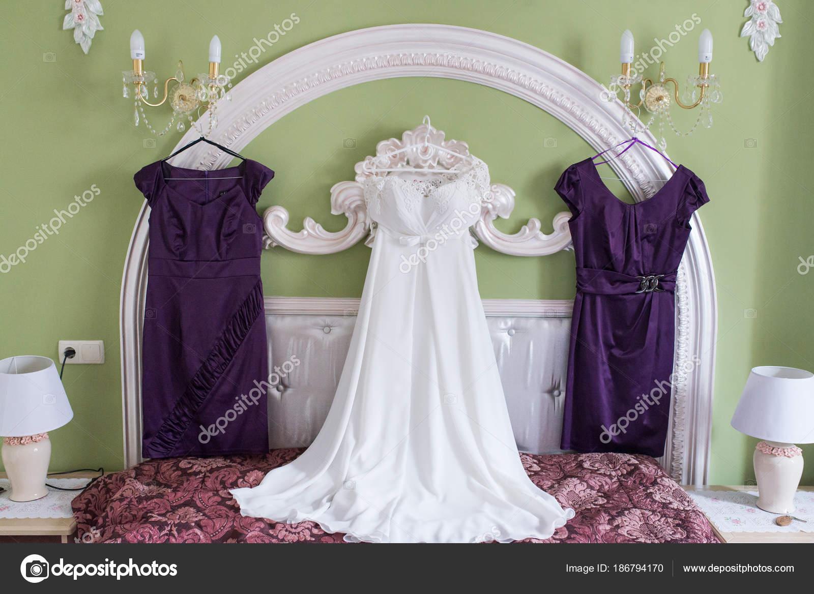 Weißes Brautkleid Und Zwei Lila Brautjungfern Kleider Auf Einem ...
