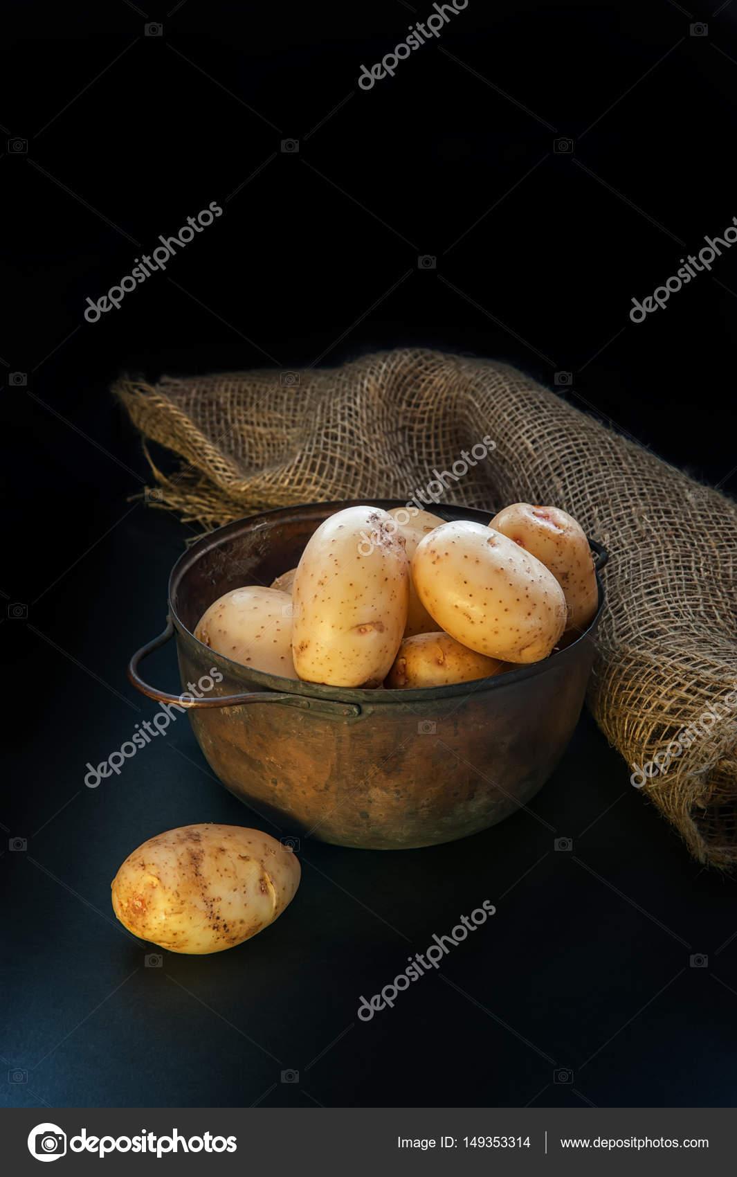 ronde gele aardappelen liggen in de pot en op tafel de verlichting ...